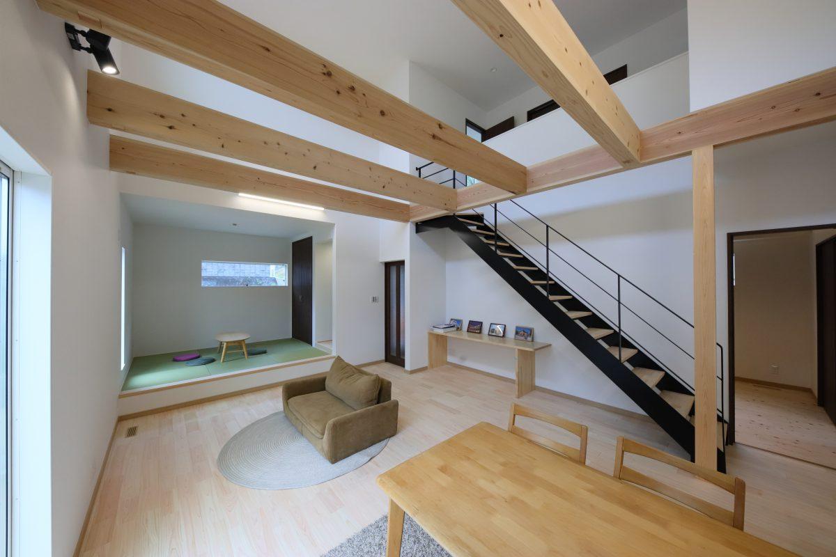 吹抜けのあるリビングには、大きな梁とオーナー様こだわりのストリップ階段がカフェのような雰囲気を演出